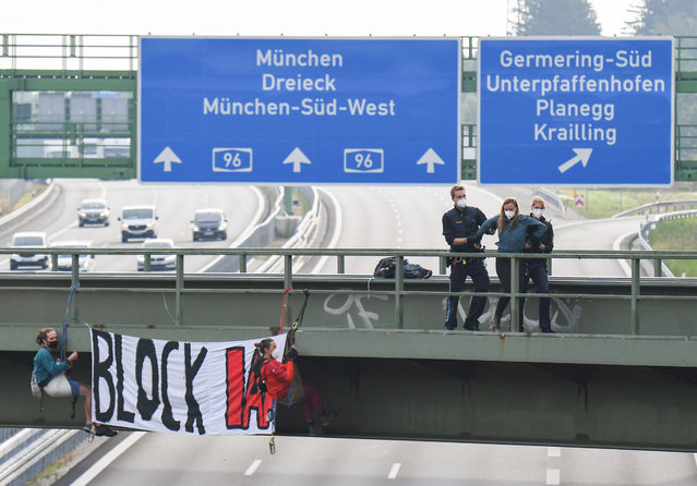 """Police detain a climate activist of Extinction Rebellion who were abseiling from a bridge over a motorway near Munich with a banner reading """"Block IAA"""" in order to block the access to the International Motor Show (IAA) held in Munich, southern Germany, on September 7, 2021. Germany's revamped IAA auto show, one of the world's largest, officially opened in Munich for a celebration of all things car-related, but climate concerns and pandemic woes threaten to spoil the party. (Photo by Tobias Schwarz/AFP Photo)"""