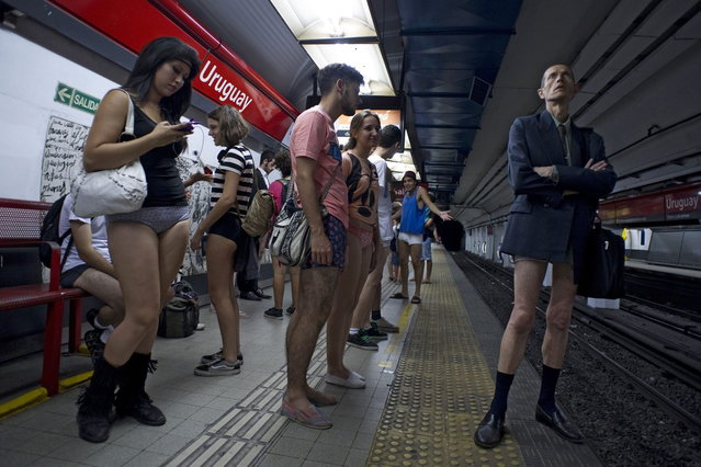 """People taking part in the """"No Pants Subway Ride"""" wait at a metro station in Buenos Aires on January 12, 2014. (Photo by Alejandro Pagni/AFP Photo)"""