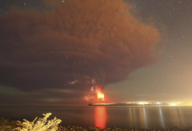 Smoke and lava spew from the Calbuco volcano, as seen from the shores of Lake Llanquihue in Puerto Varas, April 23, 2015. (Photo by Carlos Gutierrez/Reuters)