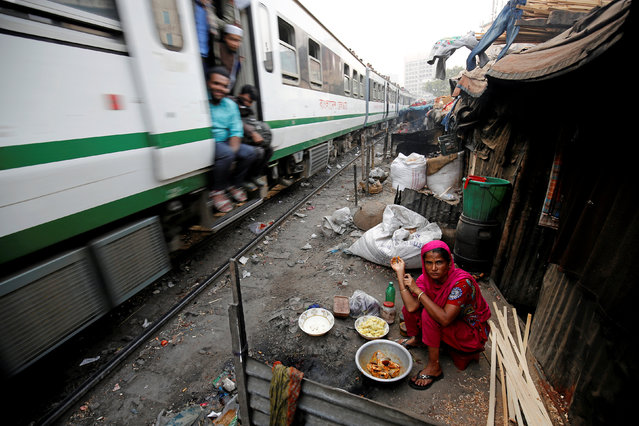 A woman reacts to the camera while preparing to cook, next to a railway track in Kawran Bazar, as a train passes by in Dhaka, Bangladesh January 17, 2017. (Photo by Mohammad Ponir Hossain/Reuters)
