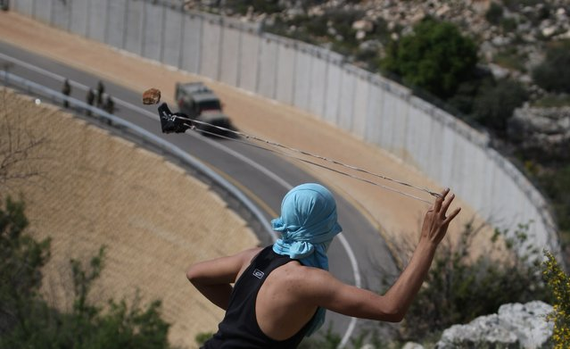 A Palestinian youth readies to sling a stone at Israeli  soldiers as they patrol along the controversial Israeli built separation barrier during clashes close to the village of Bilin, just west of the city Ramallah, in the occupied Israeli West Bank, on April 13, 2012. (Photo by Abbas Momani/AFP Photo)