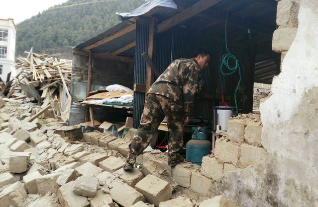 A rescuer looks at a damaged house, after a 7.9 magnitude earthquake hit Nepal, in Xigaze Prefecture, Tibet Autonomous Region, China, April 25, 2015. (Photo by Reuters/Stringer)