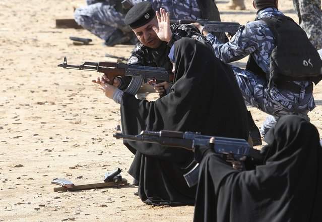 Female police trainees and their male counterparts practise firing their weapons at a shooting range during a refresher training programme in Najaf January 20, 2014. (Photo by Alaa Al-Marjani/Reuters)