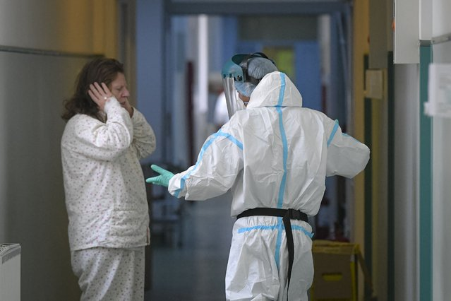 A patient complains about the noise from life support equipment to a member of the medical staff outside a COVID-19 ICU unit at the Marius Nasta National Pneumology Institute in Bucharest, Romania, Wednesday, October 6, 2021. Romania is facing an accelerated increase of daily COVID-19 infections with 14744 new cases in the last 24 hours and 331 reported deaths, the highest ever number of fatalities in one day, as authorities report they ran out of COVID-19 ICU beds at national level . (Photo by Andreea Alexandru/AP Photo)