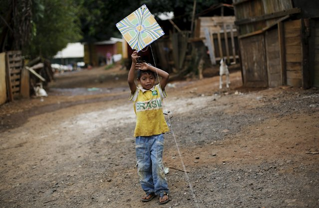 A Guarani Indian boy plays with a kite in the village of Pyau at Jaragua district, in Sao Paulo April 30, 2015. (Photo by Nacho Doce/Reuters)