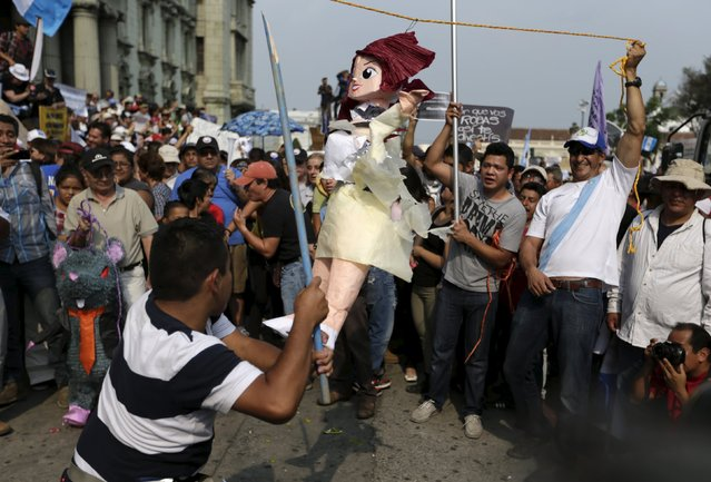 A man uses a stick to hit a pinata representing Guatemalan Vice President Roxana Baldetti during a demonstration against a political corruption scandal, in downtown Guatemala City, April 25, 2015. (Photo by Jorge Dan Lopez/Reuters)