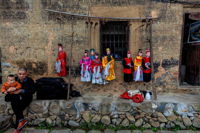 A man with child seats next to puppets on the string in front of Tulou house in Nanjing County, Fujian Province, China, 01 March 2019 (issued 20 March 2019). Fujian Tulou houses (tolou literal translation would be earthen) were built among rice, tea and tobacco fields and oldest one's date from 12th century. They are several stores high built in inward-looking circular or square shape. This layout was chosen for defense reasons as well as so that members of family or clan, who lived inside, could feel equal among each other's. Bigger ones could accommodate up to 800 people so they were organized as a small fortified cities with school and temple in the central open courtyard, halls, storehouses, wells and living areas around them on the ground floor. Today most of the Tulou hoses are still inhabited by inheritors of original builders, and except farming the lands around them and trading, they are opened to tourists, so most of the Tulou's can be visited. In 2008, 46 Fujian Tulou sites were inscribed by UNESCO as World Heritage Site.Residents of Tulou houses are happy to tell and explain to visitors a story that in 1980's American CIA thought Tulou houses were nuclear silos when they saw them from the satellite, so they send a man pretending to be a photographer with his wife who was Chinese origin to inspect them. Story is told and heard with a smile on faces from people on the both sides, showing their doubt in the story and questioning if it's just a tourist bait fairy tale. (Photo by Aleksandar Plavevski/EPA/EFE)