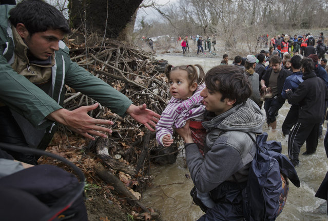 A man reaches to take a child as migrants  cross a river, north of Idomeni, Greece, attempting to reach Macedonia on a route that would bypass the border fence, Monday, March 14, 2016. (Photo by Vadim Ghirda/AP Photo)
