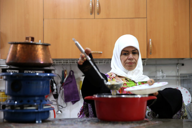 In this picture taken on Thursday, January 28, 2015, Zohreh Etezadossaltaneh ladles soup into a bowl for lunch at her home, in Tehran, Iran. (Photo by Ebrahim Noroozi/AP Photo)