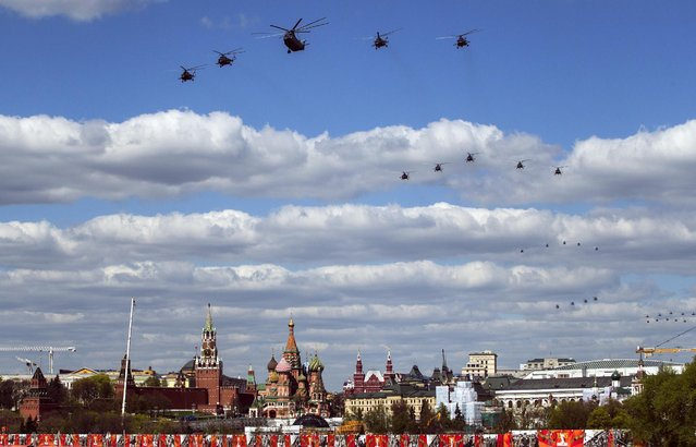 Russian army helicopters fly over Moscow during a rehearsal for the Victory Day military parade which will take place at Moscow's Red Square on May 9 in Moscow, Russia, Tuesday, May 5, 2015. (Photo by Pavel Golovkin/AP Photo)
