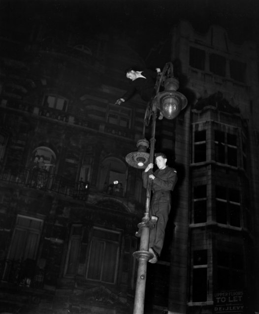 Two men climb a lamppost during nighttime VE Day celebrations in the West End of London, England, on May 7, 1945. (Photo by AP Photo)