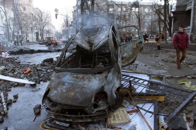 Burnt out vehicles remain after protesters clashes withpolice in Kiev on February 18, 2014. Police on Tuesday fired rubber bullets at stone-throwing protesters as they demonstrated close to Ukraine's parliament in Kiev, an AFP reporter at the scene said. Police also responded with smoke bombs after protesters hurled paving stones at them as they sought to get closer to the heavily-fortified parliament building. (Photo by Anatolii Boiko/AFP Photo)