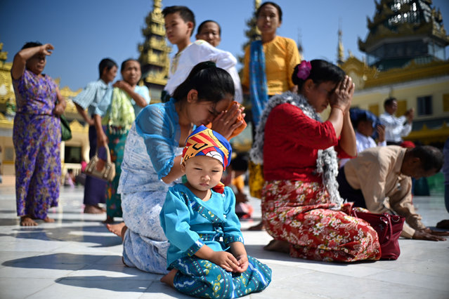 A child join other devotees praying at the Shwedagon Pagoda in Yangon, Myanmar on February 20, 2019. (Photo by Jewel Samad/AFP Photo)