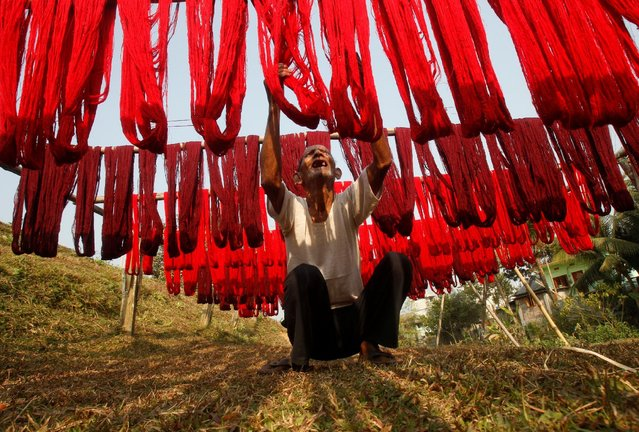 A worker hangs dyed yarn to dry at a textile mill on the outskirts of Agartala, India, February 7, 2017. (Photo by Jayanta Dey/Reuters)