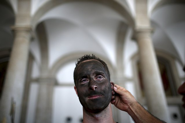 A masked man is painted before the parade of the 10th International Festival of the Iberian Mask in Lisbon, Portugal May 9, 2015. (Photo by Rafael Marchante/Reuters)