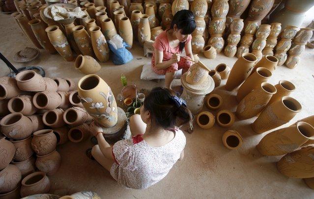 Women paint pottery jars at a factory at Phu Lang pottery village in Bac Ninh province, Vietnam, May 14, 2015. (Photo by Reuters/Kham)