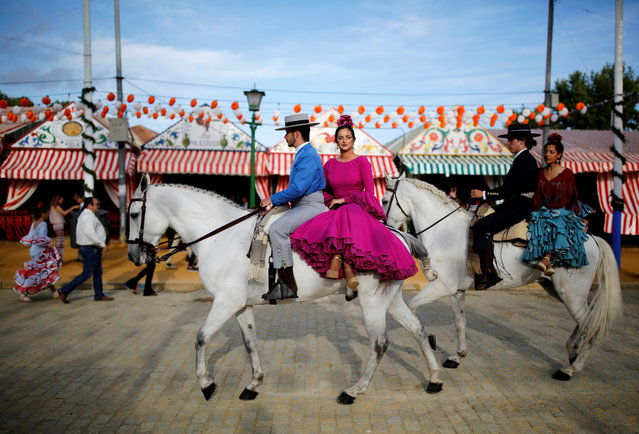 Riders wearing Andalusian outfits and women wearing sevillana dresses ride during the traditional Feria de Abril (April fair) in the Andalusian capital of Seville, southern Spain, May 9, 2019. The fair will run until May 11. (Photo by Marcelo del Pozo/Reuters)