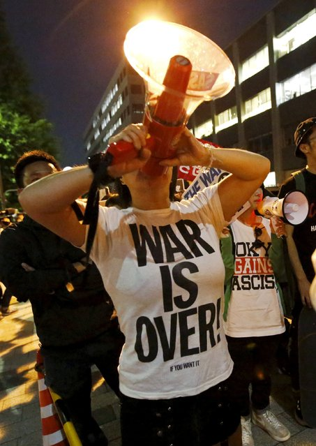 A protester shouts slogans throught a megaphone during a rally against Japan's Prime Minister Shinzo Abe's cabinet to approve Japan security bills, in front of Abe's official residence in Tokyo May 14, 2015. Japan's cabinet approved on Thursday bills to implement a drastic shift in security policy allowing the military to fight abroad for the first time since World War Two, although the public is divided and wary over the changes. (Photo by Toru Hanai/Reuters)