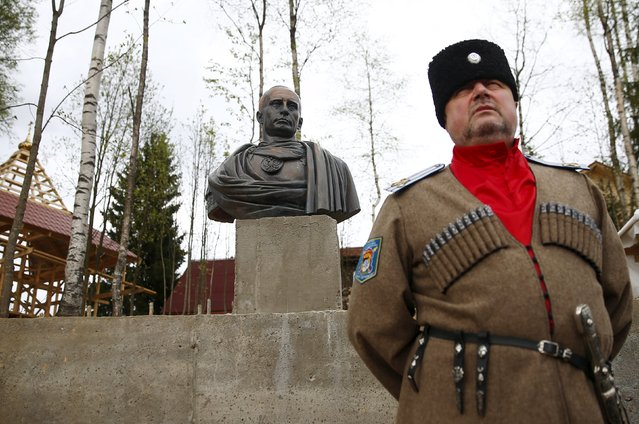 "Leader of Orthodox Cossack Union ""Irbis"" Andrei Polyakov stands next to a bust of Russian President Vladimir Putin which depicts him as a Roman emperor, during its unveiling ceremony in Leningrad region, Russia, May 16, 2015. (Photo by Maxim Zmeyev/Reuters)"