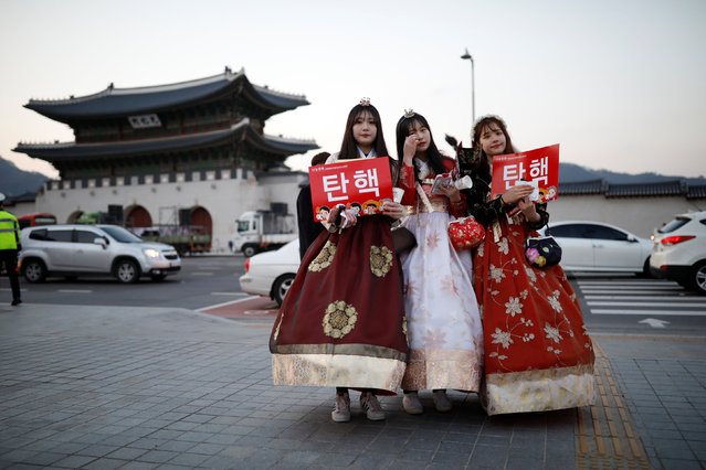 """Women wearing a Korean traditional costume Hanbok attend a protest demanding South Korean President Park Geun-hye's resignation on the occasion of the fourth anniversary of her inauguration, in Seoul, South Korea, February 25, 2017. The sign reads """"Impeachment"""". (Photo by Kim Hong-Ji/Reuters)"""