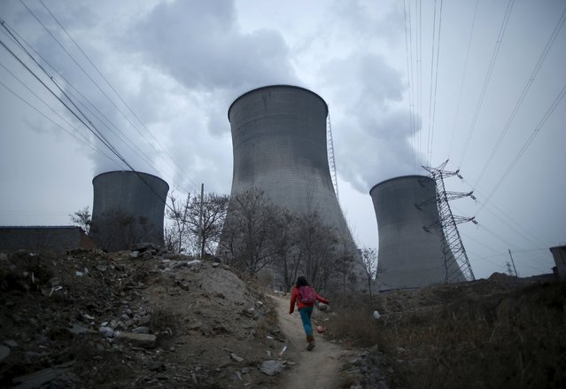 A girl makes her way to her house which locates next to chimneys of coal-fired power plant in Shijiazhuang, Hebei province, China, January 28, 2015. (Photo by Kim Kyung-Hoon/Reuters)
