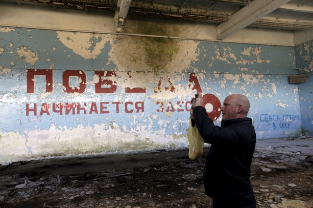 "A man takes a picture inside sports hall in the ghost town of a former Soviet military radar station near Skrunda, Latvia, April 9, 2016. The words on the wall reads in Russian ""Victory starts here"". (Photo by Ints Kalnins/Reuters)"