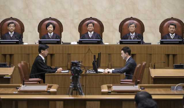 South Korean Chief Justice of the Supreme Court Kim Myeongsu, center, sits with other justices upon their arrival at the Supreme Court in Seoul, South Korea, Thursday, November 1, 2018. South Korea's top court has ruled that people can legally reject mandatory military service on conscientious or religious grounds and must not be punished. (Photo by Yun Dong-jin/Yonhap via AP Photo)