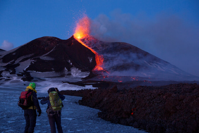 Volcano guides stand in front of Italy's Mount Etna as it spews lava during an eruption on the southern island of Sicily, Italy on March 1, 2017. (Photo by Antonio Parrinello/Reuters)