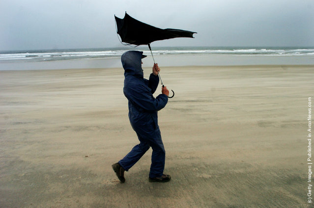Doris Pennman adjusts her umbrella as she walks along Mission Beach