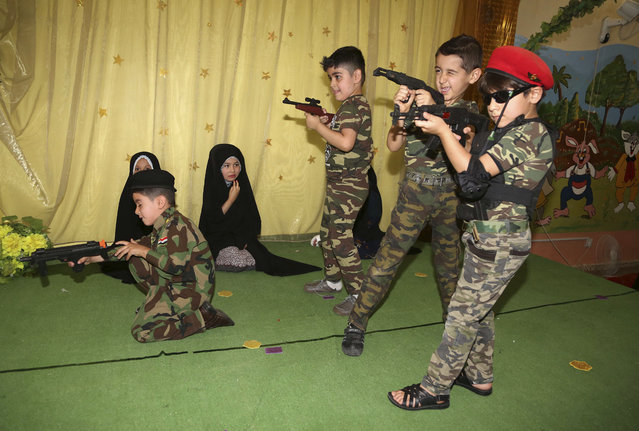 """Iraqi students act a scene from a play titled """"We are all against terrorism"""", at a government primary school in Baghdad, Iraq, Tuesday, May 19, 2015. Children play the roles of government forces and militants from the Islamic State group. (Photo by Karim Kadim/AP Photo)"""