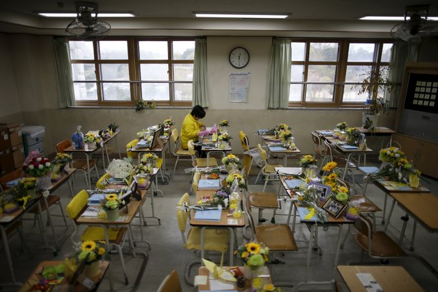 A mother of a victim who was onboard sunken ferry Sewol, leaves a message on a desk used by her child at an empty classroom, which was preserved since the disaster, at Danwon high school during the second anniversary of the disaster in Ansan, South Korea, April 16, 2016. (Photo by Kim Hong-Ji/Reuters)