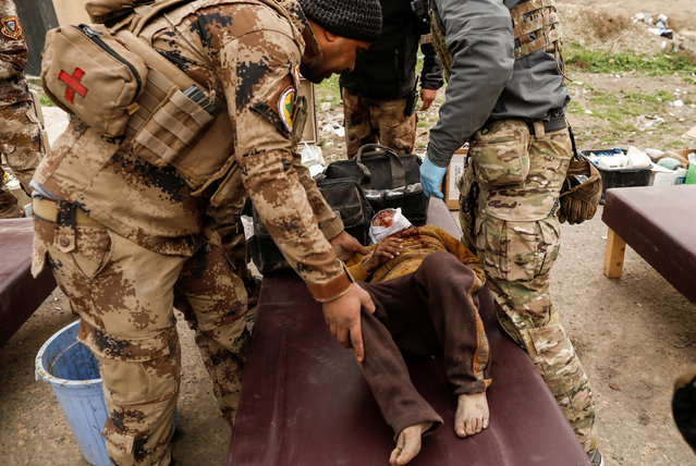 A boy injured in a mortar attack is treated by medics in a field clinic as Iraqi forces battle with Islamic State militants, in western Mosul, Iraq March 2, 2017. (Photo by Zohra Bensemra/Reuters)
