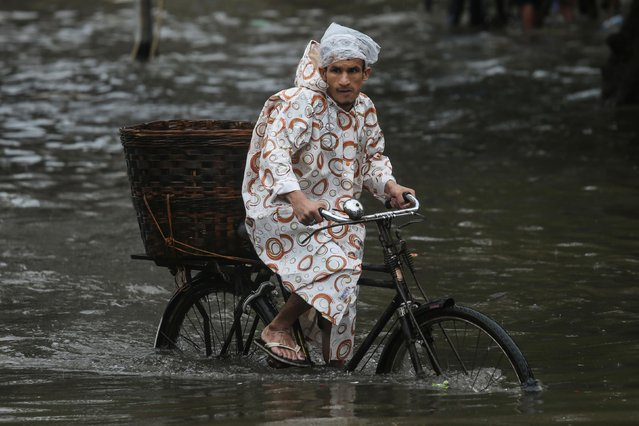 A man rides a bike through a water-logged street during heavy rains in Mumbai, July 1, 2019. (Photo by Francis Mascarenhas/Reuters)