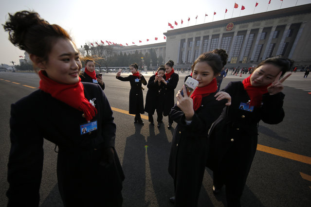 Bus ushers take selfies on an empty street adjacent to the Great Hall of the People during the Chinese People's Political Consultative Conference (CPPCC) in Beijing, Friday, March 3, 2017. Thousands of delegates have gathered at the Chinese capital for the opening of the annual session of the Chinese People's Political Consultative Conference, which advises the rubberstamp parliament, whose annual session begins Sunday. (Photo by Andy Wong/AP Photo)
