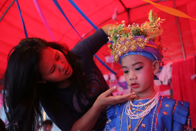 A Tai Yai boy is dressed and made-up elaborately during the Poy Sang Long festival on April 7, 2014 in Mae Hong Son, Thailand. Poy Sang Long is a Buddhist novice ordination ceremony of the Shan people or Tai Yai, an ethnic group of Shan State in Myanmar and northern Thailand. Young boys aged between 7 and 14 are ordained as novices to learn the Buddhist doctrines. It's believed that they will gain merit for their parents by ordaining. (Photo by Taylor Weidman/Getty Images)
