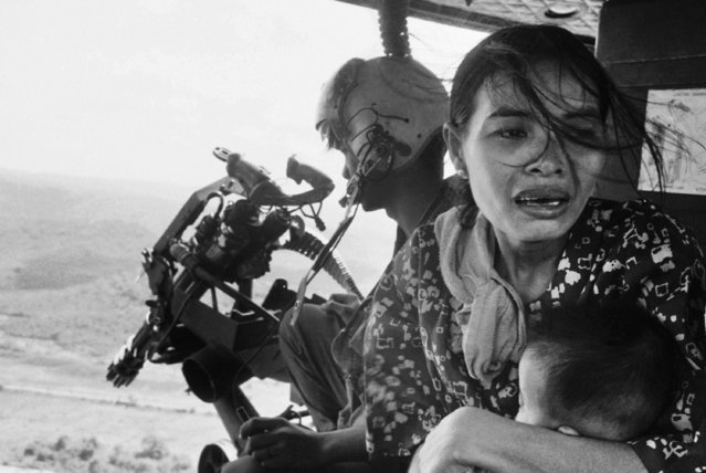 In this March 22, 1975 file photo, a refugee clutches a baby as a government helicopter gunship carries them away near Tuy Hoa, Vietnam, 235 miles northeast of Saigon. They were among thousands fleeing from Communist advances. (Photo by Nick Ut/AP Photo)