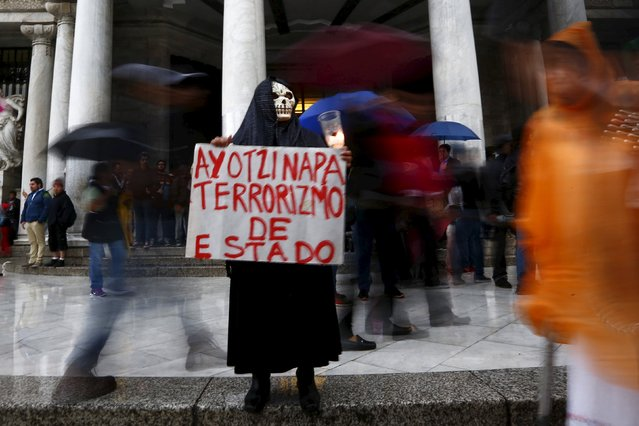 A demonstrator holds a sign during a protest to mark the nine-month anniversary of the Ayotzinapa students' disappearance in Mexico City June 26, 2015. The students' disappearance on the night of September 26, 2014 in the southwestern city of Iguala triggered massive protests in Mexico and calls for justice. (Photo by Edgard Garrido/Reuters)