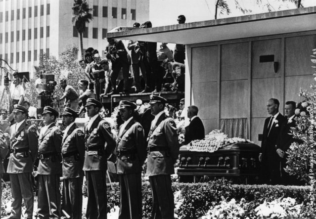 Detectives from the Pinkerton Agency in powder-blue uniforms with white silk scarves at their throats guard the coffin of American actress Marilyn Monroe, in Westwood Memorial Park, Hollywood, not far from the orphanage where she was brought up