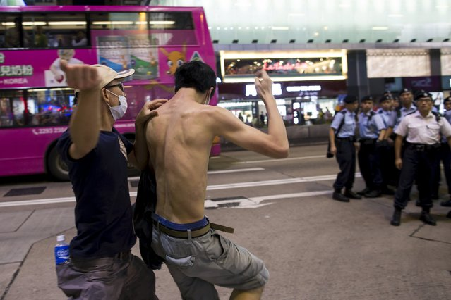 A pro-China demonstrator (L) hits a localist protester as police standing guard on the street look on during an anti-China protest at Mongkok shopping district in Hong Kong, China June 28, 2015. The police later broke up the fight, but did not detain either man. (Photo by Tyrone Siu/Reuters)
