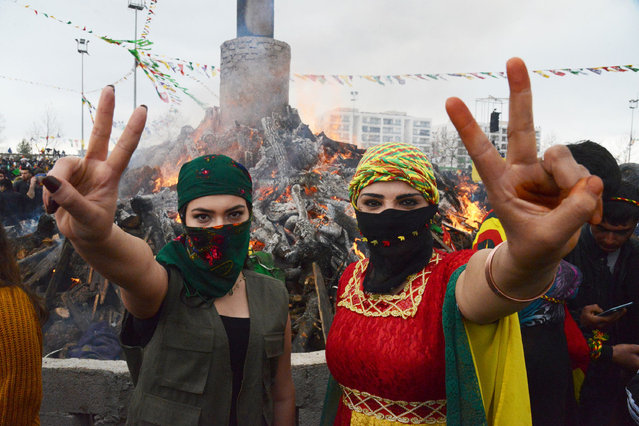 Young women flash the victory sign in front of a bonfire as Turkish Kurds gather during Newroz celebrations for the new year in Diyarbakir, southeastern Turkey, on March 21, 2017. Newroz (also known as Nawroz or Nowruz) is an ancient Persian festival, which is also celebrated by Kurdish people, marking the first day of spring, which falls on March 21. (Photo by Ilyas Akengin/AFP Photo)