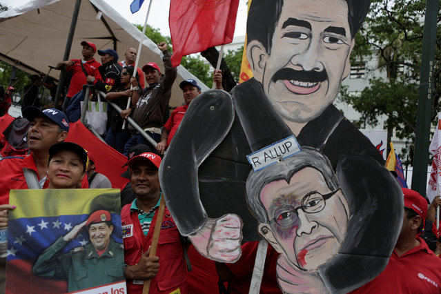 Supporters of Venezuela's President Nicolas Maduro hold up a cardboard figure of him and Henry Ramos Allup, President of the National Assembly and deputy of the Venezuelan coalition of opposition parties (MUD) during a rally to commemorate May Day, in Caracas, Venezuela, May 1, 2016. (Photo by Marco Bello/Reuters)
