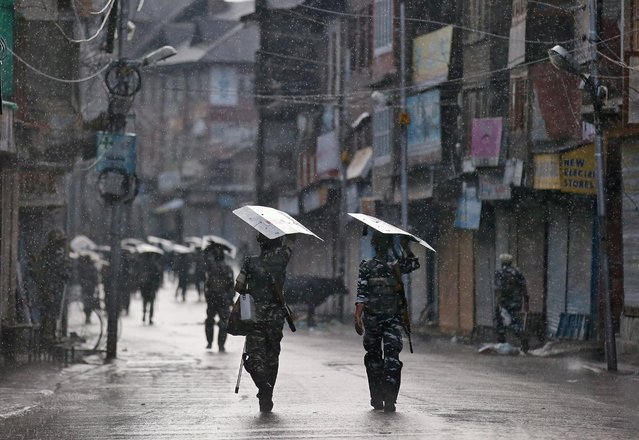 Indian security forces personnel patrol a deserted street during restrictions after the government scrapped special status for Kashmir, as it rains in Srinagar August 8, 2019. (Photo by Danish Ismail/Reuters)