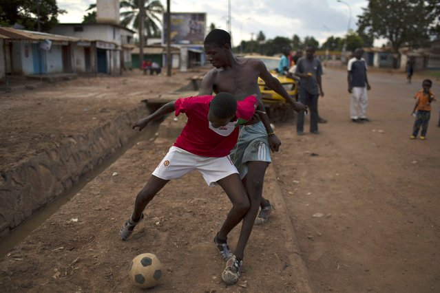 Boys play soccer on the main street of Kilometre 5 (PK5), a predominately Muslim neighbourhood of the capital Bangui April 23, 2014. (Photo by Siegfried Modola/Reuters)