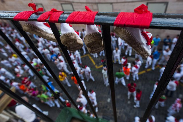 San Fermin's espadrilles hang from a balcony on Santo Domingo street, during the running of the bulls at the San Fermin Festival, in Pamplona, Spain, Tuesday, July 7, 2015. (Photo by Alvaro Barrientos/AP Photo)
