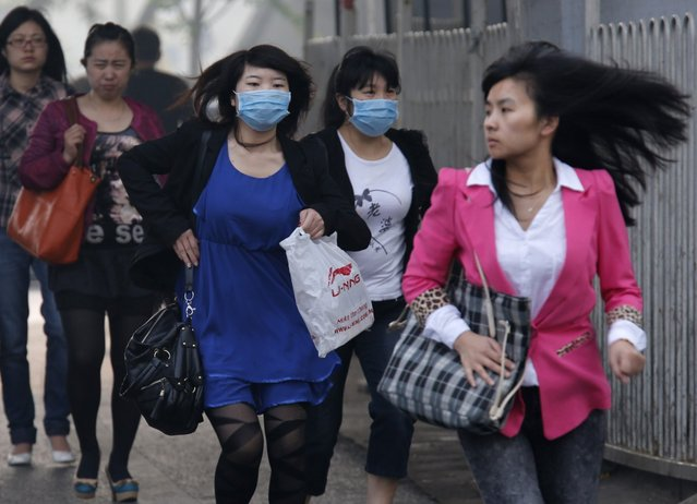 """Women wearing face masks run to cross a street in Beijing May 6, 2013. The United States Embassy monitor on air quality in China classified the quality of air in Beijing as """"hazardous"""". (Photo by Kim Kyung-Hoon/Reuters)"""
