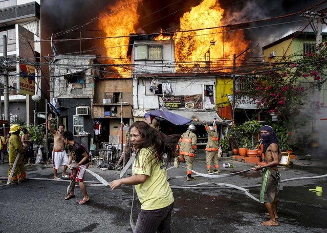 Residents help firemen in putting out fire that engulfs a poor neighborhood in Manila, Philippines, on March 29, 2014. Authorities said three people died in the hour-long fire that razed more than a dozen homes and displaced several families. (Photo by Bullit Marquez/Associated Press)