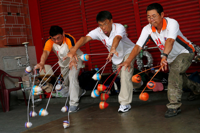 Members of the Sanxia Pinpoint Spinning Top Team throw 18 spinning tops simultaneously at Sanxia old street in New Taipei City, Taiwan May 8, 2016. (Photo by Tyrone Siu/Reuters)