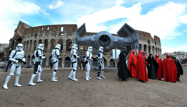"Members of the Star Wars fan club celebrate ""Star Wars Day"" in front of the Colosseum in central Rome on May 4, 2014. (Photo by Tiziana Fabi/AFP Photo)"