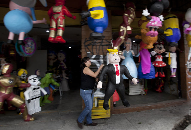 """Alicia Lopez Fernandez hangs to dry her recently made piñata in the likeness of Donald Trump at her family's store """"Piñatas Mena Banbolinos"""" in Mexico City, Friday, July 10, 2015. The piñata was a special order made after Trump's comments that some Mexican immigrants to the U.S. bring drugs and crime, and some are rapists. (Photo by Marco Ugarte/AP Photo)"""