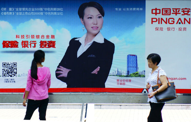 People walk past an advertisement of Ping An, in Yichang, Hubei province, China, in this August 19, 2015 file photo. (Photo by Reuters/Stringer)